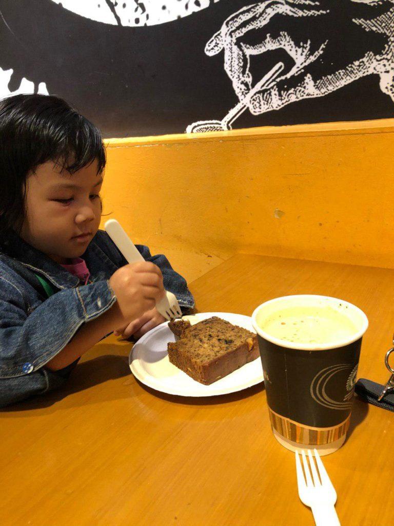 Sambil menunggu flight, kill the time dengan minum kopi. Sarah makan kek pisang